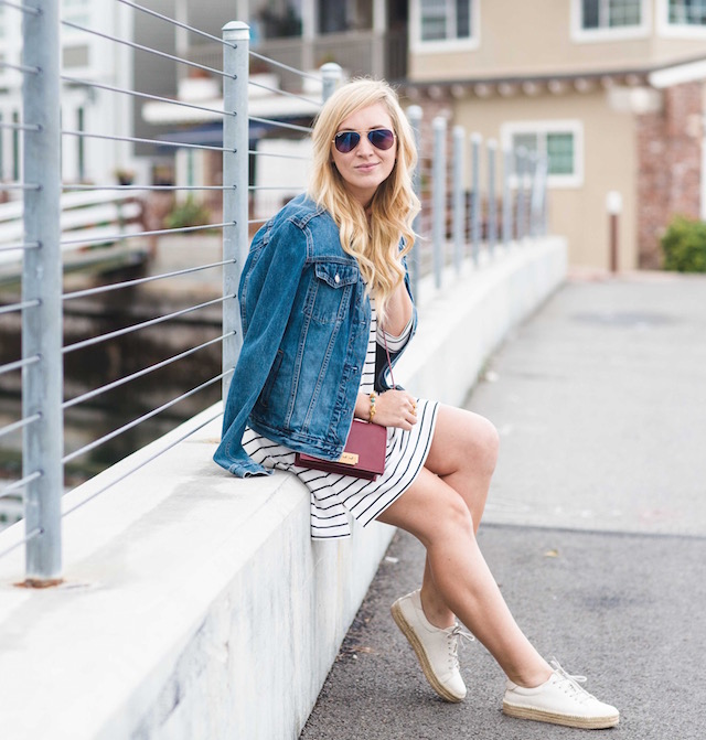Orange County fashion blogger Nikki Prendergast of My Style Diaries wears a classic striped dress, denim jacket, and sneakers.